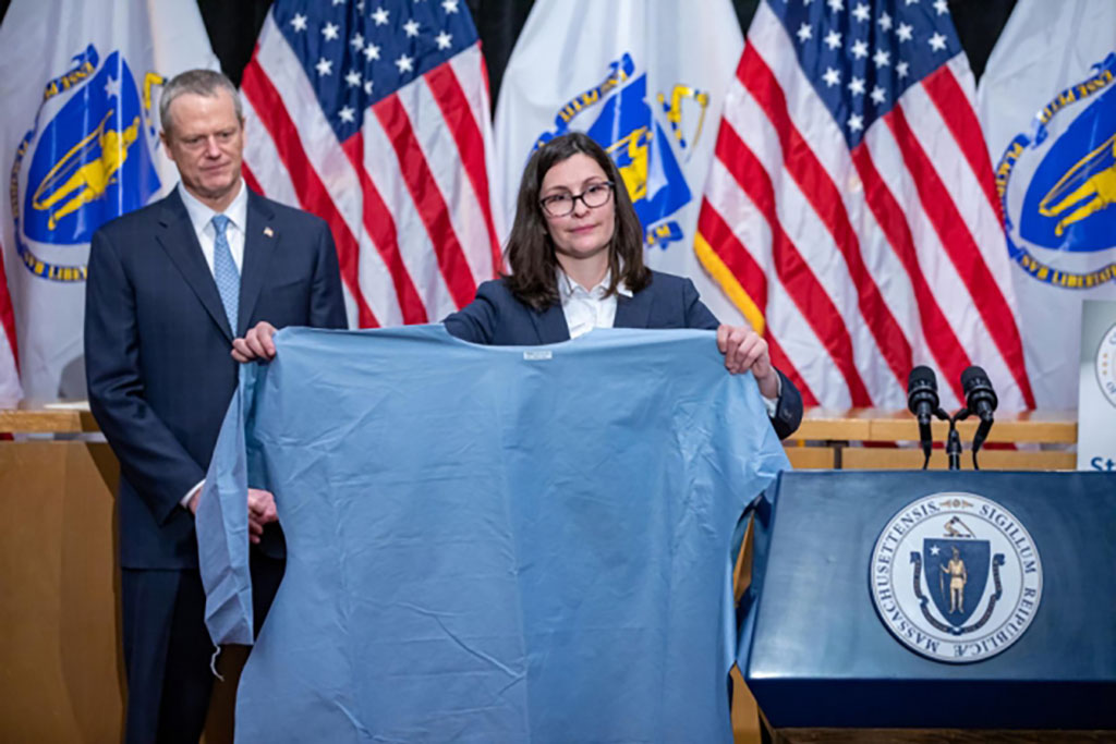 This photo, from April 13, 2020, shows Gov. Charlie Baker, left, and Brenna Schneider, CEO of 99Degrees, who holds one of the hundreds of thousands of medical isolation gowns her company has produced with support from M-ERT.