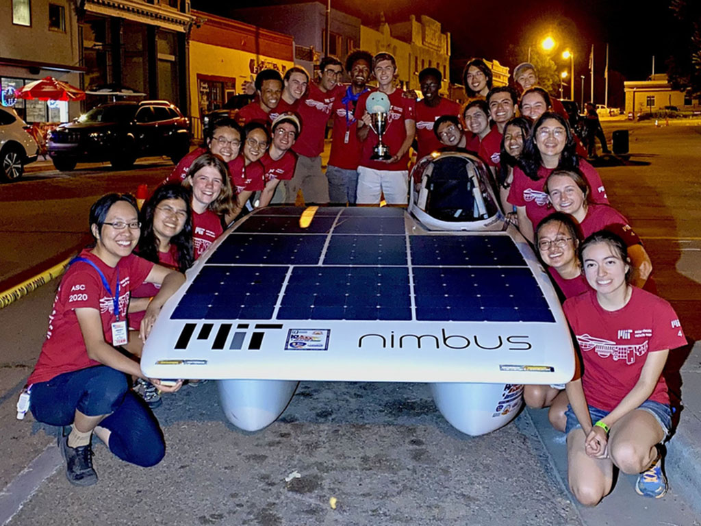 Caption:The MIT Solar Electric Vehicle Team poses with Nimbus, their solar car, after winning the 2021 American Solar Challenge.