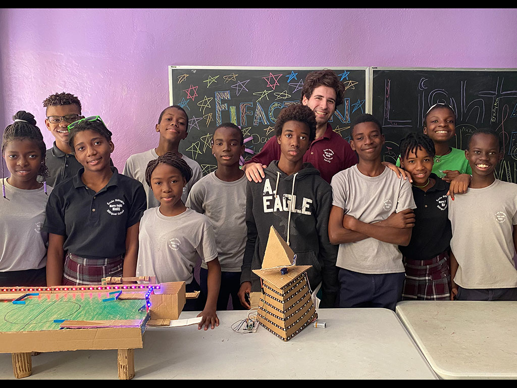 Caption:Mechanical engineering student, Eli Brooks, taught engineering toy design to children at the Have Faith Haiti Mission & Orphanage in Port-au-Prince, Haiti. Here, Brooks (back row, center) poses with his middle school class before they presented th